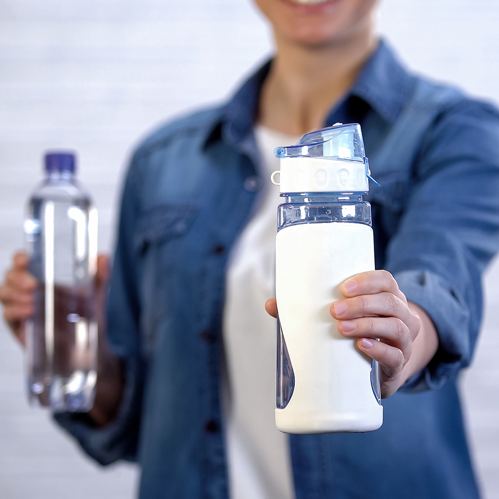 Female choosing reusable thermos instead disposable bottle, plastic pollution